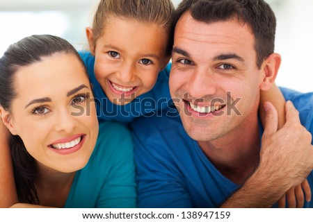 cute family of three face closeup portrait at home - stock photo
