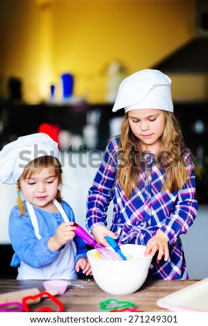 cute family of two girls wearing chef hats baking in the kitchen indoor - stock photo
