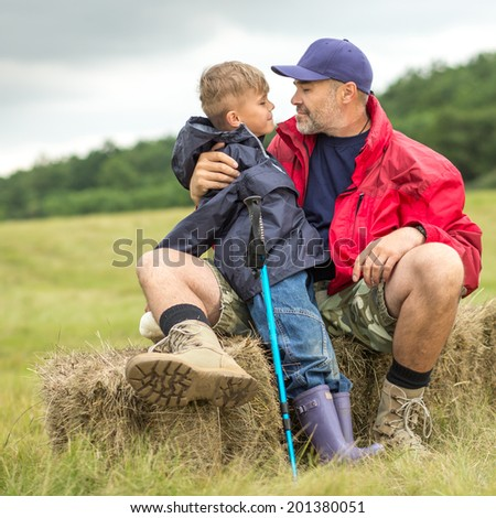 Cute family on a trekking day. Father and son relaxing after a forest and plain trail, focus on father - stock photo