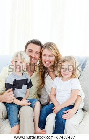 Cute family on their sofa at home - stock photo