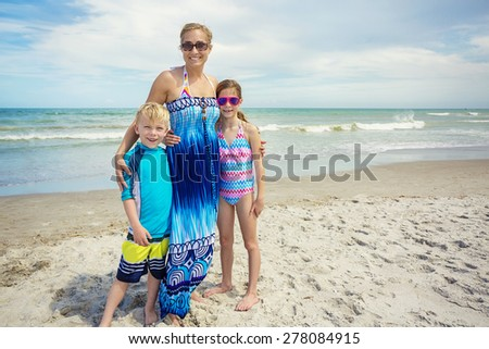 Cute family portrait on a beautiful beach. Horizontal photo of an attractive Mother and her two kids on beautiful beach day with the ocean in the background. Lots of copy space - stock photo