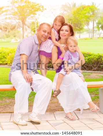 Cute family sitting on bench in the park, active lifestyle, little brother and sister with parent outdoors, parenthood concept