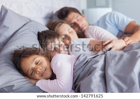 Cute family sleeping together in bed - stock photo