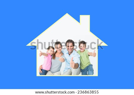 Cute family smiling at camera together showing thumbs up against blue vignette - stock photo