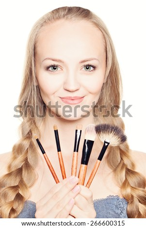 Cute fashion woman holding makeup brushes  - stock photo