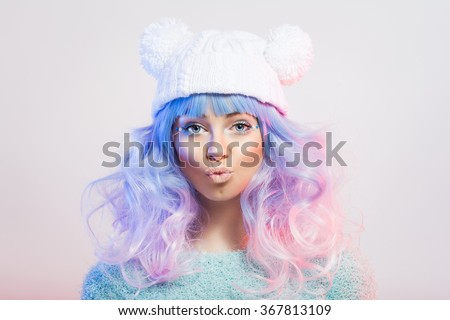 Cute fashionable young woman with pastel purple and pink hair and makeup in fun white knitted beanie hat. Teenage girl with colorful luscious hair pouting and posing. Closeup, studio shot, retouched. - stock photo