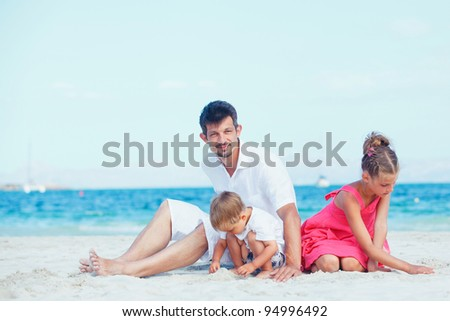 Cute father and her child playing happily at pretty beach