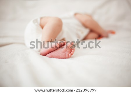 Cute feet of newborn baby sleeping on the bed - stock photo