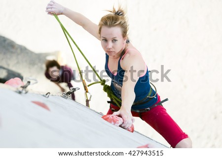 Cute female Athlete hanging on climbing Wall holding Rope in left Hand and belaying Partner watching from below. National Climbing competitions, Dnipro, Ukraine, May 20, 2016 - stock photo