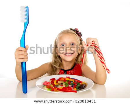 cute female child eating dish full of sweets and holding huge toothbrush in dental care and health concept and unhealthy sugar abuse isolated on white background - stock photo