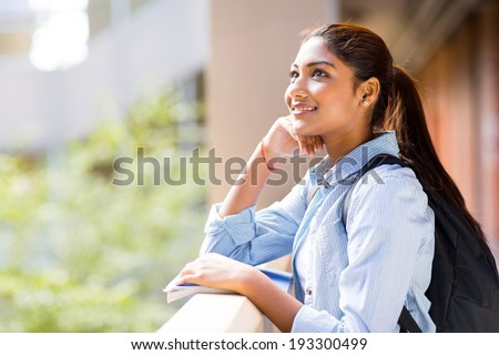 cute female college student looking up - stock photo