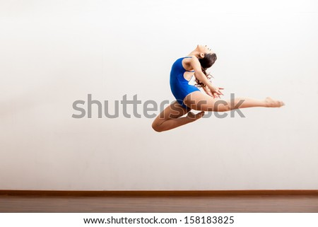 Cute female dancer in a leotard practicing a big jump of her dance routine in a studio