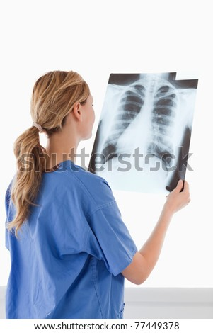 Cute female doctor looking at an X-ray on a white background