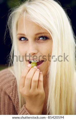 Cute female eating a grape - stock photo
