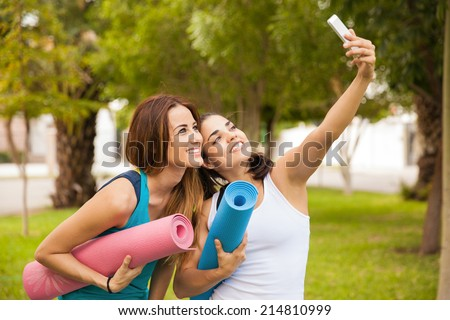 Cute female friends taking a selfie with their smart phone while doing yoga at a park - stock photo