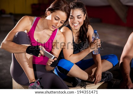 Cute female friends texting and social networking at a gym - stock photo