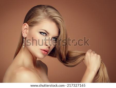 Cute female model holding her gorgeous hair wearing brilliant earrings. - stock photo