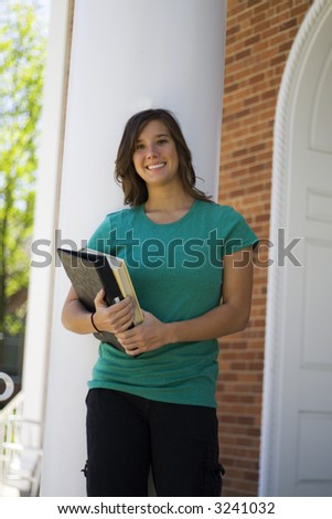 Cute female on the steps of a classroom building on campus