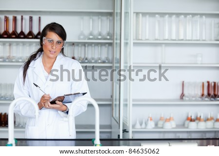 Cute female scientist writing on a clipboard while looking at the camera - stock photo