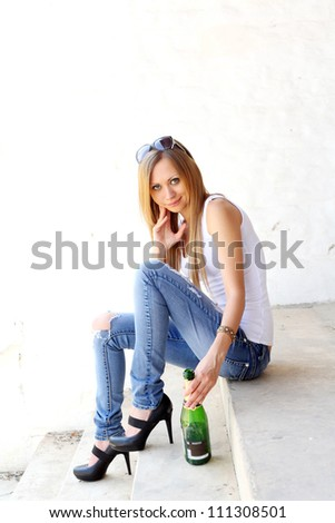 Cute female sitting on the stairs with bottle of vine - stock photo