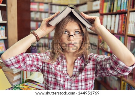 Cute female student in high school or university library getting knowledge from the book. Funny blond Caucasian girl in eyeglasses looking up. - stock photo