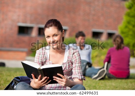 Cute female student reading a book sitting on grass in the campus of her university - stock photo