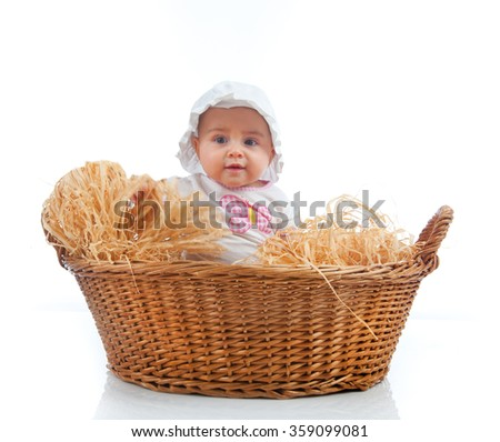 Cute female toddler in a straw basket on white background - stock photo