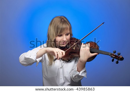 Cute female violinist playing on the violin with blue background - stock photo