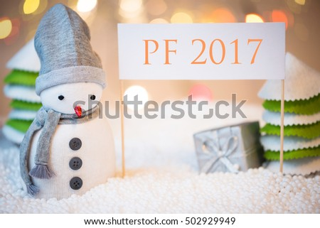 Cute festive snowman with PF 2017 sign, Christmas lights in background