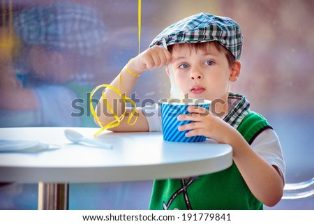 Cute fie years boy eating ice cream at indoor cafe - stock photo