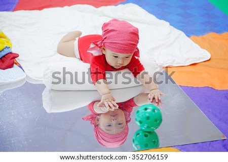 Cute five months asian baby playing ball on mirror in colorful playroom - stock photo
