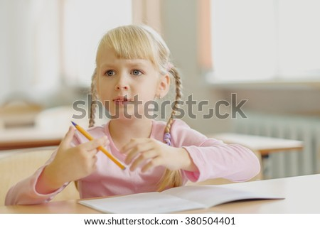Cute five years old  blonde girl sitting at classroom and writing - stock photo