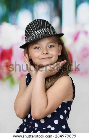 Cute flirtatious long haired girl  in polka-dot dress and hat portrait - children beauty and fashion concept - stock photo
