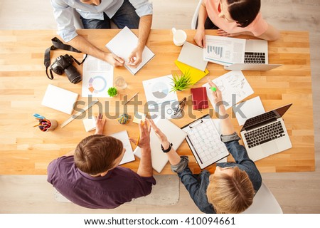 Cute four colleagues are working in cooperation - stock photo