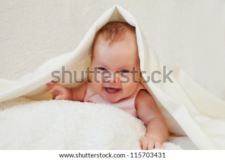 Cute four month old baby girl is under white blanket - stock photo