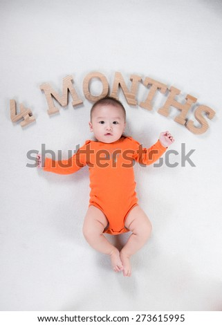 cute four month old baby lying on blanket bed at home. Looking up with surprised expression. - stock photo