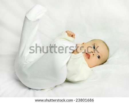 cute four months old baby boy lies on the white sofa - stock photo