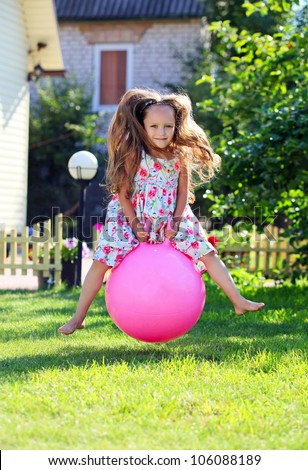 Cute four-year girl bouncing on a big ball in a front yard - stock photo