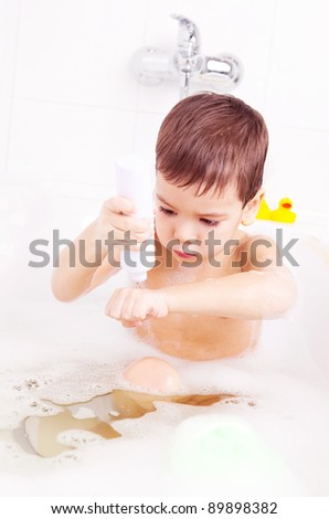 cute four year old boy taking a  bath with foam and using cosmetics