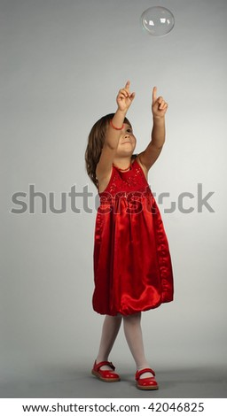 Cute four-year-old girl in red dress and red shoes pointing at soap bubble - stock photo