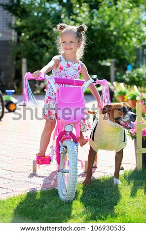 Cute four-year old girl on a bicycle with her staffordshire terrier dog - stock photo