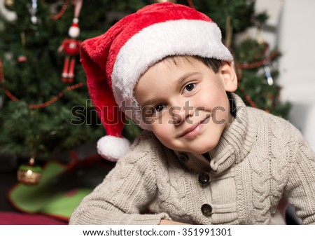 Cute four years old boy in Santa hat - stock photo
