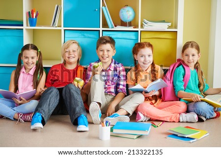 Cute friends sitting on the floor of classroom and doing schoolwork - stock photo