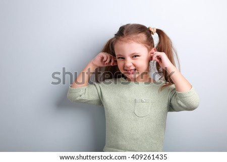 Cute fun kid girl covered ears the fingers and gesturing that not want to listen on blue background with empty copy space - stock photo