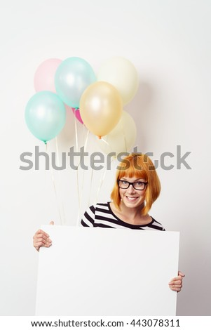 Cute fun young woman with a blank white signboard with copy space held in front of her and a colorful bunch of festive party balloons floating in the air behind - stock photo