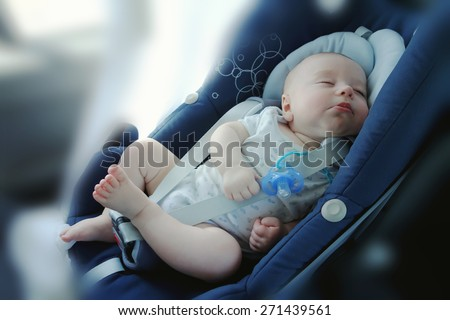 Cute funny baby boy is sleeping in car ?hild safety seat, image with toning, blur background and effect of soft shining sun - stock photo