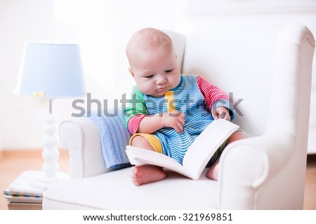 Cute funny baby boy reading a book sitting in a white chair at home. Children read books in a library seat. Nursery and playroom interior for kids. Early development and learning for young kid. - stock photo