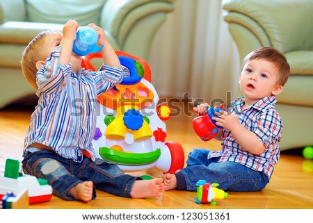 cute funny baby boys playing with toys at home - stock photo