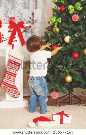 Cute funny baby decorating Christmas Tree at home.  - stock photo