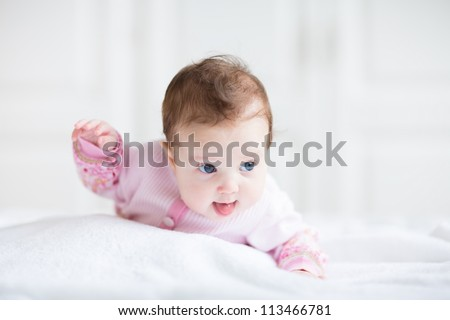 Cute funny baby girl in a pink cardigan trying to crawl - stock photo